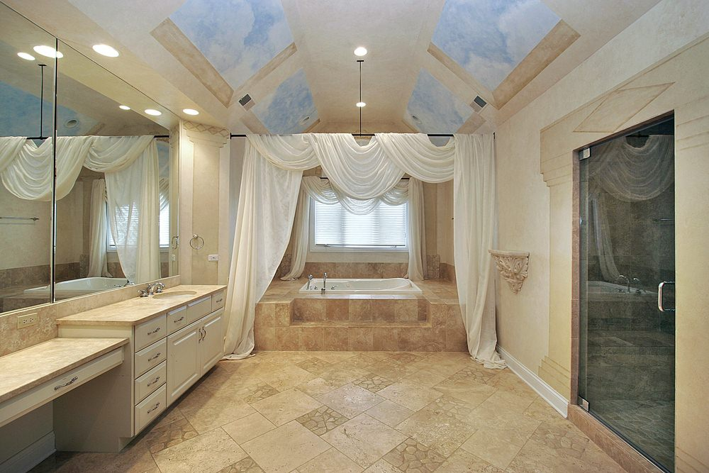 This beautiful bathroom looks like a bedroom at first glance due to its white cloth drapery that adorns the bathtub making it look like a four-poster bed. This drapery works well with the cathedral ceiling that has a mural of windows filled with a blue sky.