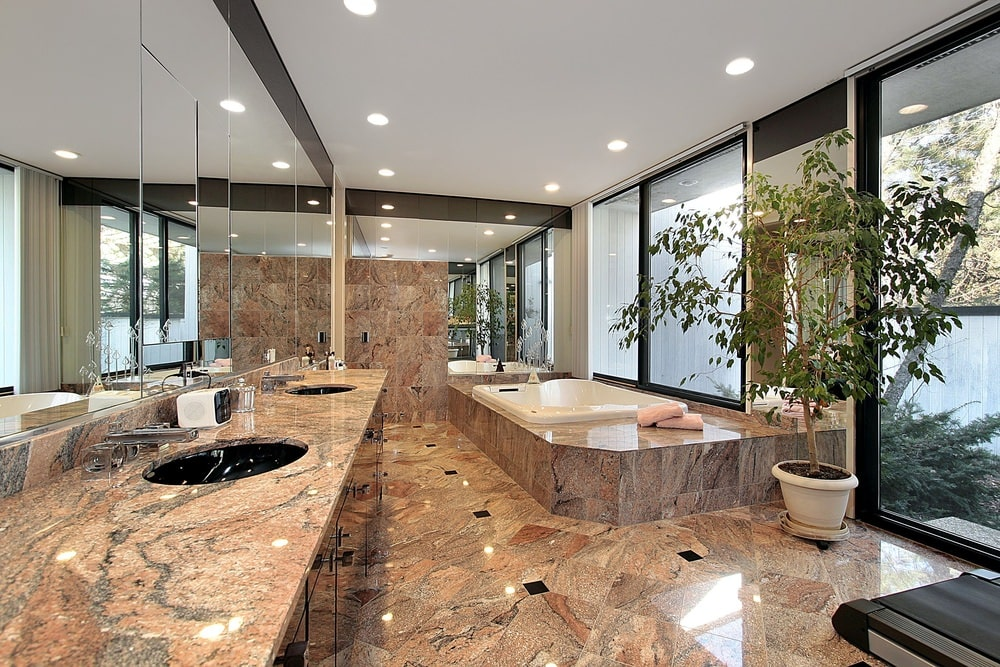 The brown marble tiles of the flooring extends to the housing of the luxurious bathtub in the corner by the window adorned with a potted plant. This matches with the countertop of the vanity that has a couple of black basin sinks topped with wide frame-less mirrors.