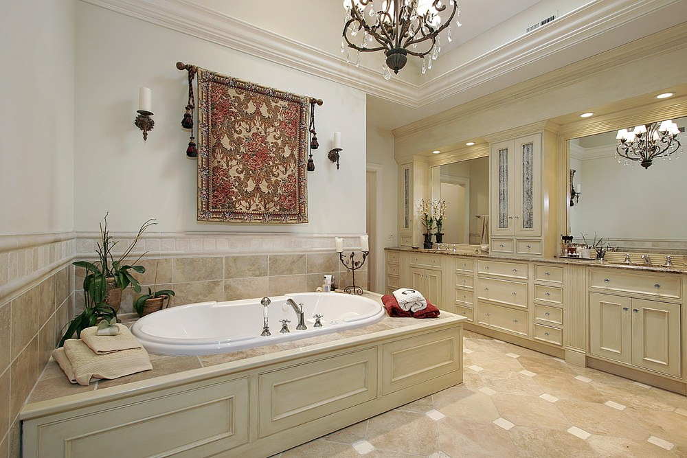The beautiful and intricate wrought iron chandelier hanging from the white ceiling matches with the wall-mounted candelabras flanking the patterned tapestry hanging above the bathtub that has a wooden housing matching the shaker cabinets and drawers of the two-sink vanity.