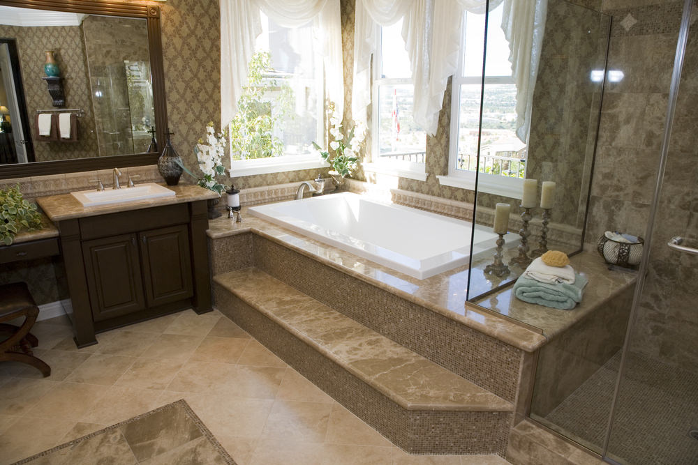 Three white windows that brighten the bathtub's corner are all paired with white curtains that contrasts the brown patterned wallpaper. This complements the dark brown wooden vanity as well as the brown marble of the bathtub, flooring and shower area.