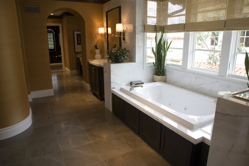 This bathroom has brown walls except for the wall that supports the dark brown vanity and bathtub with the same dark brown hue on its housing. These are all brightened by the natural light of the windows and the warm yellow light of the vanity area.