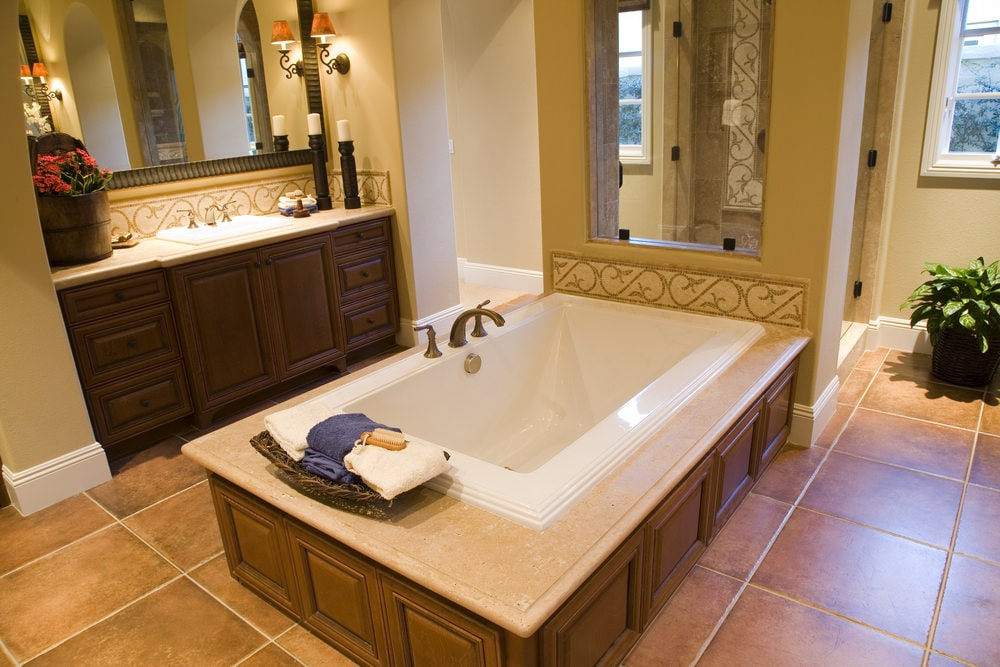 The brass faucet of the bathtub matches those of the sink housed by the wooden vanity with same dark wooden cabinets and drawers as the housing of the bathtub. This housing is attached to the wall of the shower area at the far end of the Mediterranean-style bathroom.