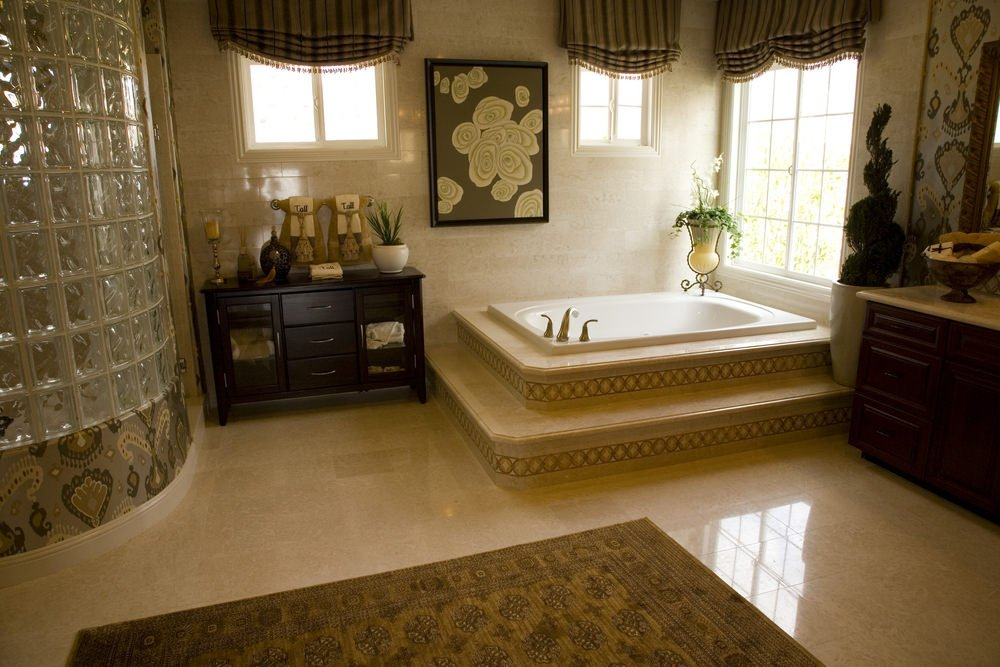 The brown patterned area rug over the beige marble flooring complements the wallpaper that frames the frosted glass wall of the shower area. This is also placed on the side of the wooden vanity between it and the corner bathtub accented with a potted plant and a painting.