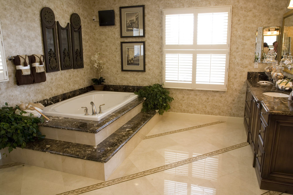 The light brown and beige elements of this Mediterranean-style primary bathroom dominate the flooring tiles and the patterned wallpaper that has a chic design. This makes the dark marble of the bathtub and the dark wooden vanity stand out.