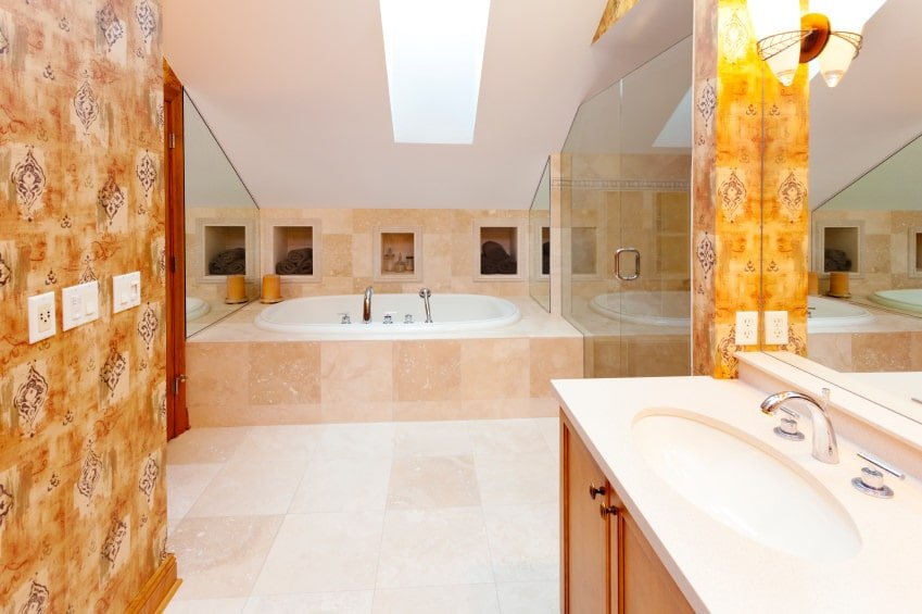 This Mediterranean-style bathroom is brightened by the white shed ceiling that has a sky light in the middle over the beige marble flooring in between the bathtub at the far end and the wooden vanity that has bright orange patterned wallpaper.