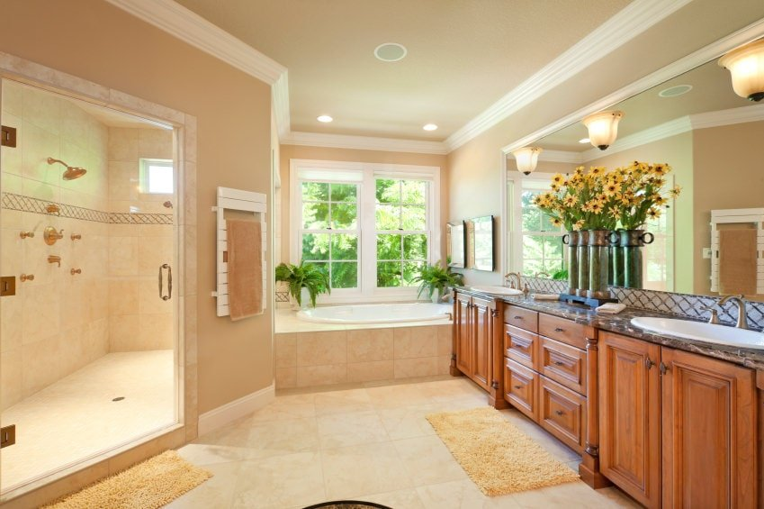 The elegant wooden shaker cabinets of the vanity has that classic look that goes well with the wide mirror above it. This is adorned with a set of flowers in vases and a trio of wall-mounted lamps. Adjacent to this vanity is the white bathtub by the window with potted ferns.