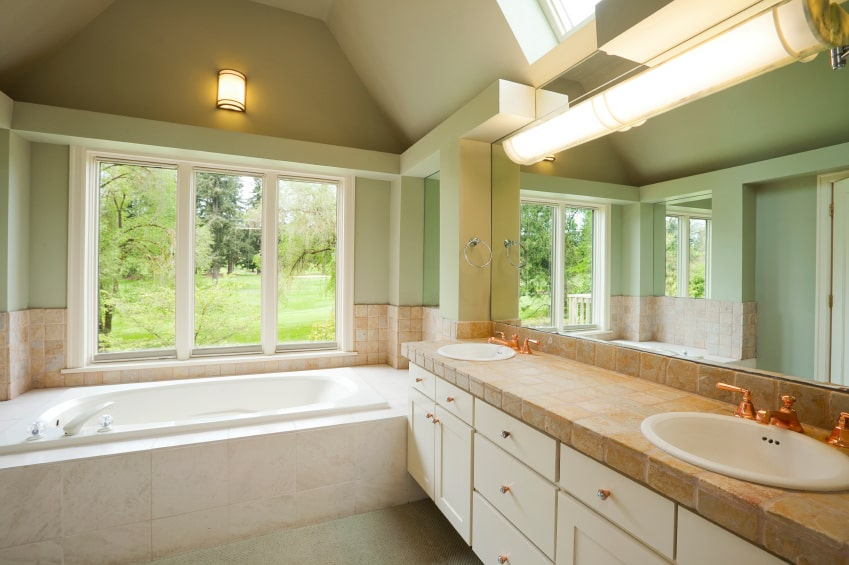 This simple bathroom has a green tinge to its cove ceiling that extends to the walls that are dominated by bright windows above the white bathtub and a large mirror above the white floating vanity that is paired with brilliant brass fixtures.
