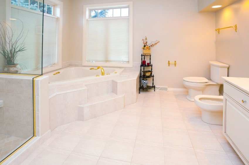 The glass enclosure of the shower area is lined with gold that pairs well with the golden faucet of the corner bathtub and the fixtures of the toilet across from the tub. This toilet area is lit by the yellow recessed lights above it bringing a beige tinge to the light gray walls.