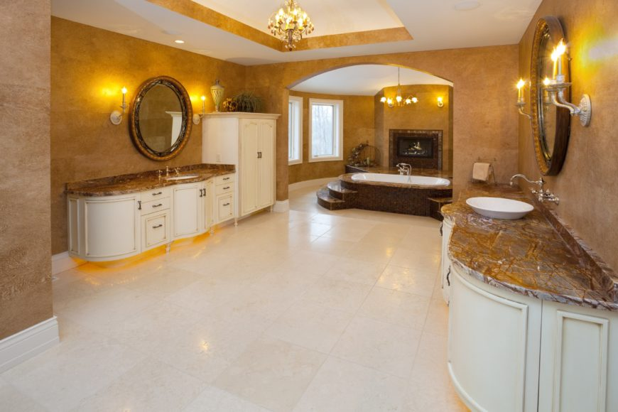 The curved white wooden vanities of this elegant Mediterranean-style bathroom are adorned with yellow lights underneath. This matches with the yellow lights of the chandelier over the bathtub that matches with the wall-mounted lamps flanking the vanity mirror.