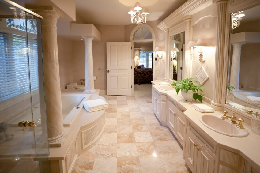 The charming wall-mounted lamps that flank the vanity mirrors are a perfect match for the simple chandelier hanging in the middle of the beige wooden vanity and the bathtub that is adorned with a couple of decorative pillars and shuttered windows.