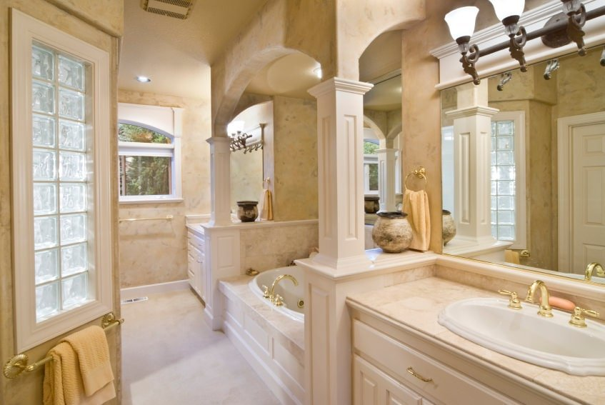 The two wooden vanities of this bathroom have light golden faucets and handles on their cabinets and drawers that go well with the light pink hue of the bathroom. These matches with the bathtub that is placed in the middle of the two vanities.
