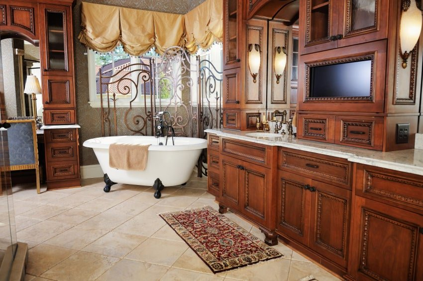 This bathroom is dominated by the elegant dark brown cabinets and drawers of the vanities that flank the white freestanding bathtub in the corner. This is adorned with dark green wallpaper, white windows and a set of shiny golden curtains.