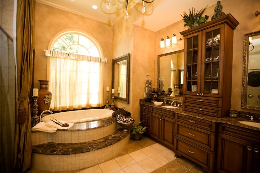 The warm yellow lights of the wall-mounted lamps above the two-sink vanity complements the dark brown wooden cabinetry as well as the beige walls above the bathtub that is adorned with candelabras, jars, mirror and even a potted plant.