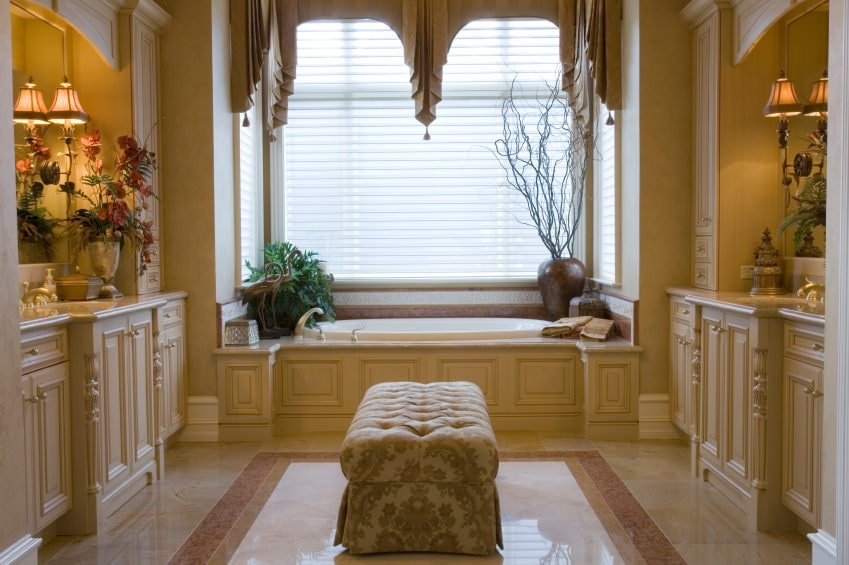 The lovely bathtub is placed in a nook below the bright windows that are subdued by its white blinds. This bathtub is adorned with a potted plant and a decorative earthy jar. This setup is a nice backdrop for the two wooden beige vanities with a cushioned bench in the middle.