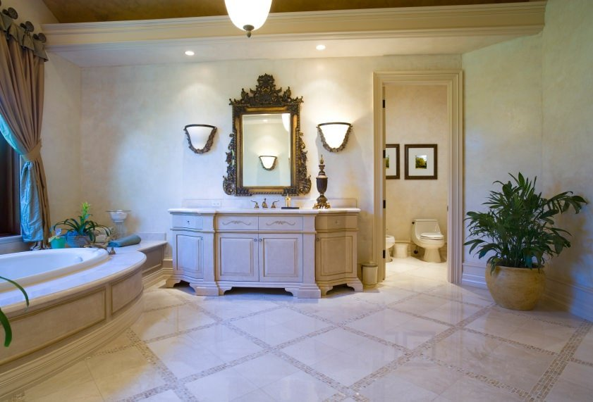 The Pendant light hanging in the middle of this Mediterranean-style bathroom matches the wall-mounted lamps that flank the intricate mirror of the light gray wooden vanity. The design of this wooden vanity matches the housing of the bathtub as well as the moldings of this Mediterranean-style bathroom.