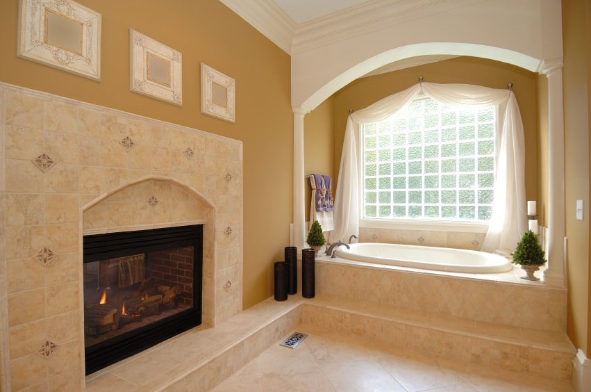 This Mediterranean-style bathroom is warmed by the fireplace that is inlaid with the same beige marble tiles as the flooring and the housing of the bathtub adjacent to it. This small nook of the bathtub is brightened by the frosted glass window and its white arch.