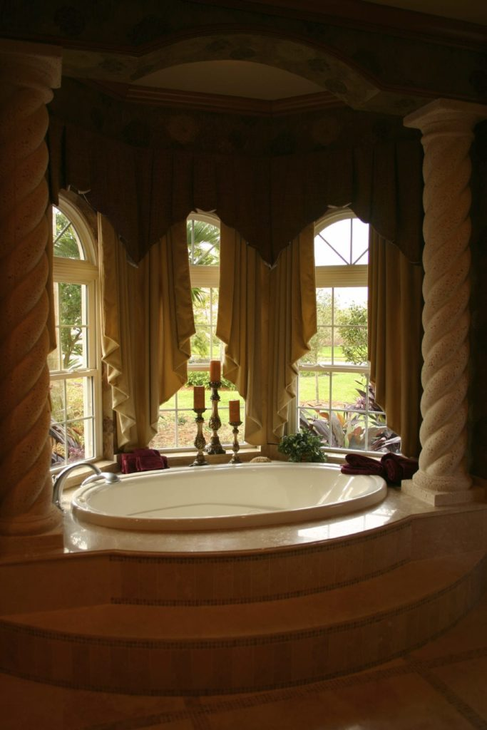 The two beautiful decorative pillars have a spiral design that complements the aesthetic of the elegant Mediterranean-style primary bathroom. The white porcelain bathtub that these pillars flank is adorned with candelabras and three arched curtained windows.