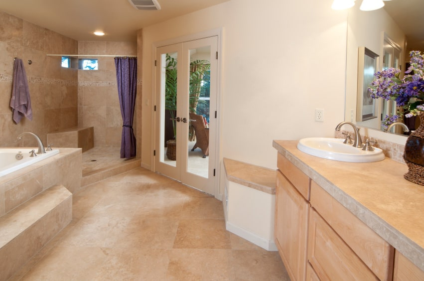 The shower area on the far corner has two narrow windows and a blue shower curtain that stands out against the beige marble tiles of the floor and the walls of the shower area. This setup is mirrored by the vanity that has beige marble countertops contrasted by the blue flowers in a vase beside its sink.