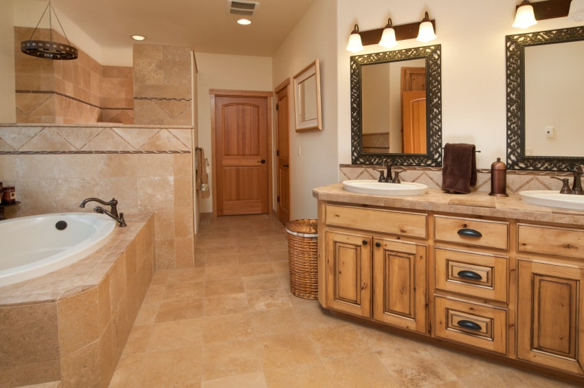 The wooden two-sink vanity of this Mediterranean-style primary bathroom follows the lay of the white walls across from the white bathtub that is surrounded by the beige marble that is perfectly paired with the flooring as well as the walls of the shower area.
