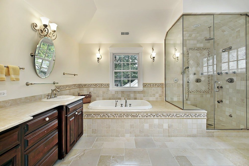 The wooden vanity of this Mediterranean-style bathroom has such an elegant design and hue to it that makes it stand out against the beige countertop that matches with those of the bathtub and the tiles of the floor that extend to the glass-enclosed shower area.