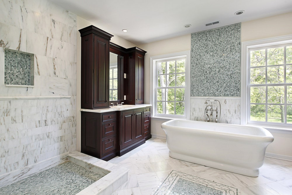 The bright white marble tiles are paired with complex patterned light gray decorative tiles that are applied to the wall above the freestanding bathtub's backsplash, on the shower area flooring and the middle of the floor. These are further brightened by the natural lights and are contrasted by the dark wooden vanity.