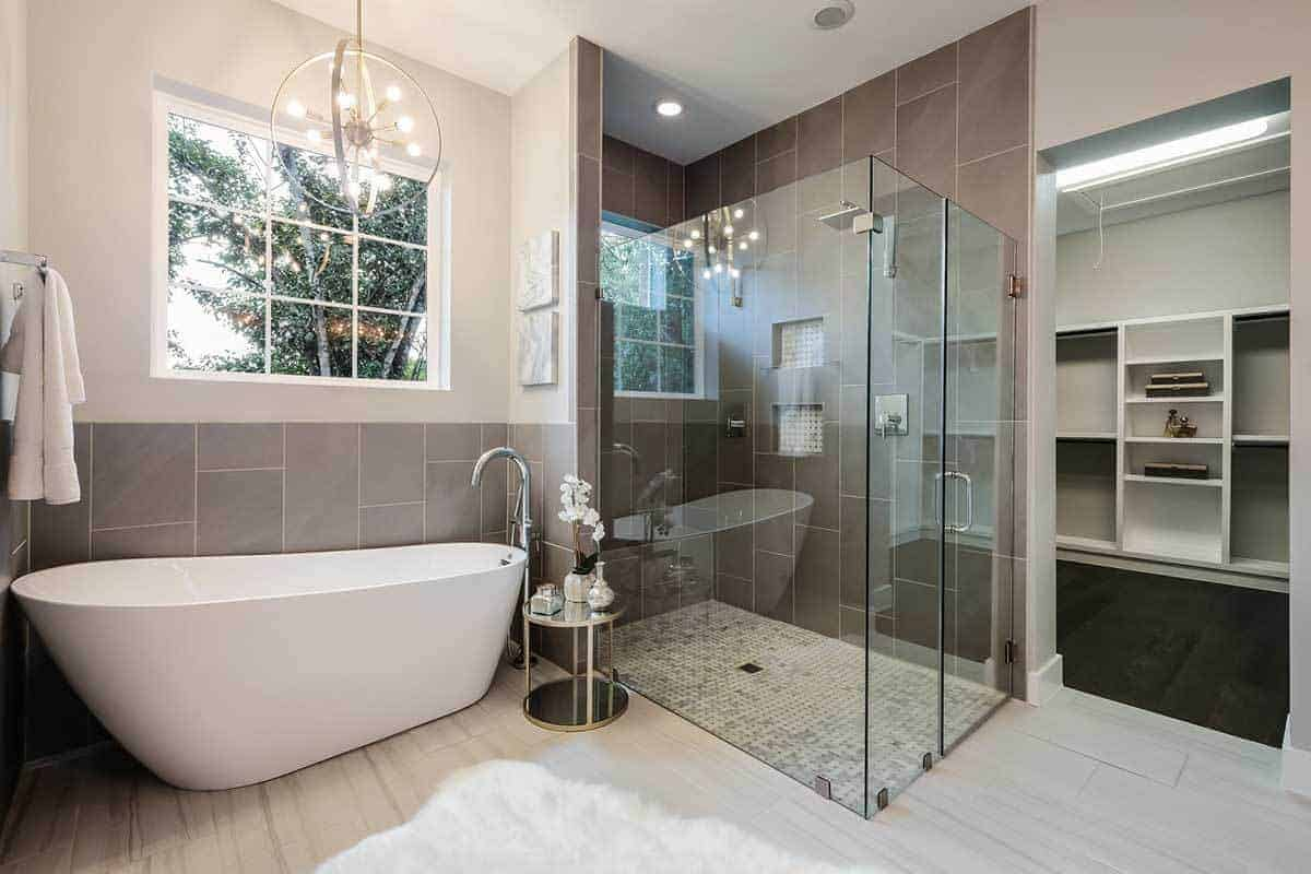 The elegant small chandelier that has a spherical design casts a white light that blends with the natural lights coming in from the window above the freestanding bathtub. This is placed in a small nook at the corner beside the walk-in glass-enclosed shower area.
