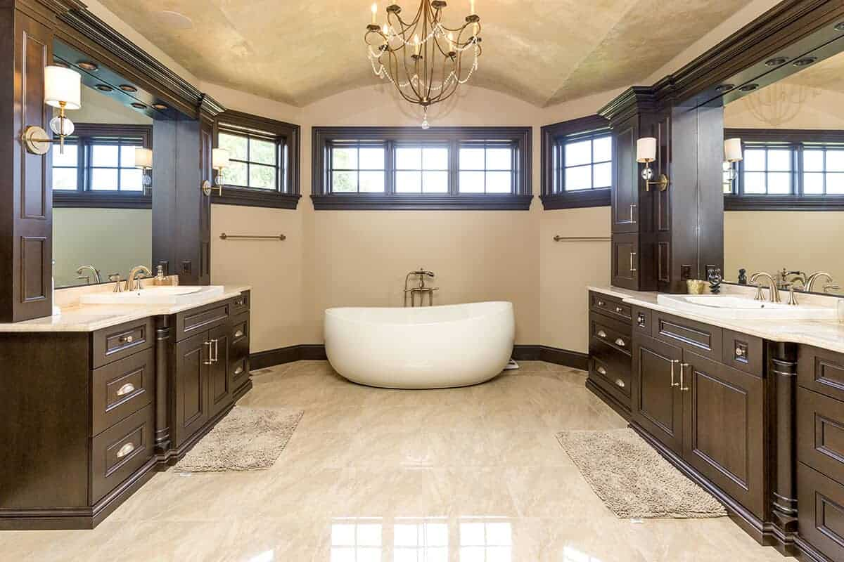 In the middle of the cove ceiling hangs a charming chandelier that matches the aesthetic of the two dark wooden structures on either side of this Mediterranean-style bathroom. These houses the two sinks and large mirrors flanking the way to the freestanding bathtub at the far wall.