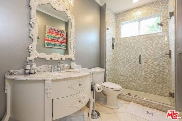 This simple and chic bathroom has an elegant white wooden vanity that has intricate and fine designs on it matching the frame designs of the wall-mounted mirror that stands out against the gray wall. This sets a nice foreground for the simple toilet and patterned walls of the walk-in shower area.