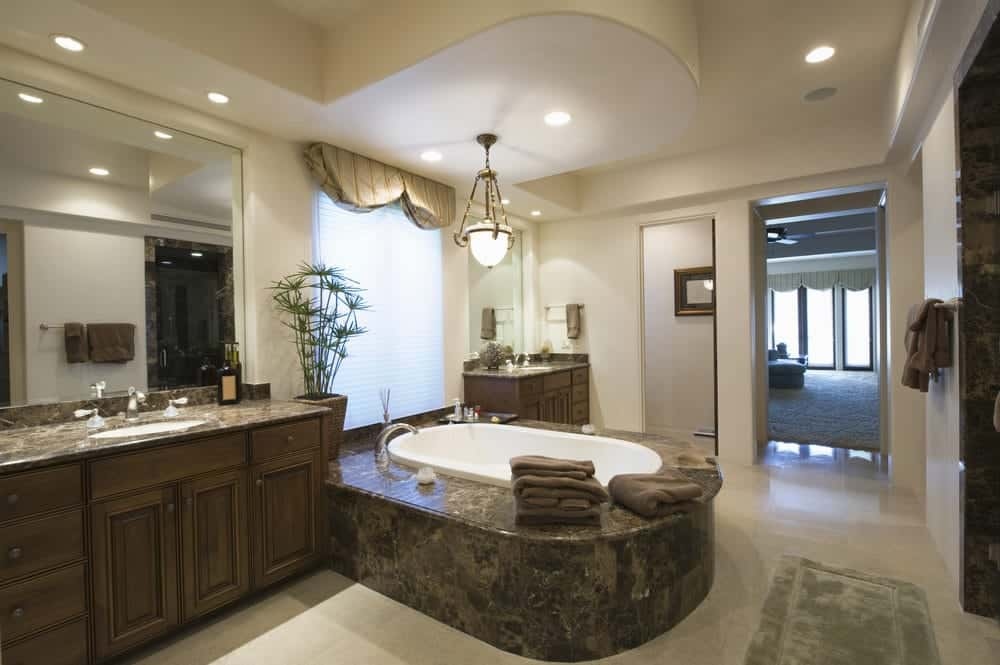 The black and brown marble housing of the bathtub stands out against the light gray flooring. This bathtub housing matches with the countertops of the dark wooden vanities that contrast the beige walls illuminated by the recessed lights and the large frosted glass pendant light over the tub.