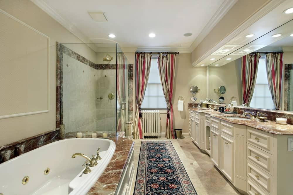 The glass-enclosed shower area stands in the corner beside the white porcelain bathtub that contrasts the brown marble inlay. This is across from the two-sink vanity with the same countertop and has beige cabinets and drawers blending with the floor and walls.