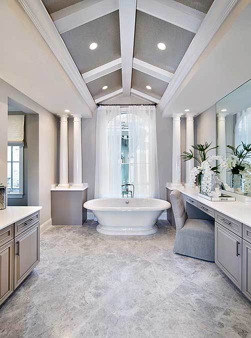 This beautiful and charming Mediterranean-style bathroom has a cathedral ceiling with white exposed beams that match the small pillars against the gray far wall flanking the freestanding bathtub. Adjacent to this is one of the gray wooden vanities that has a white countertop.