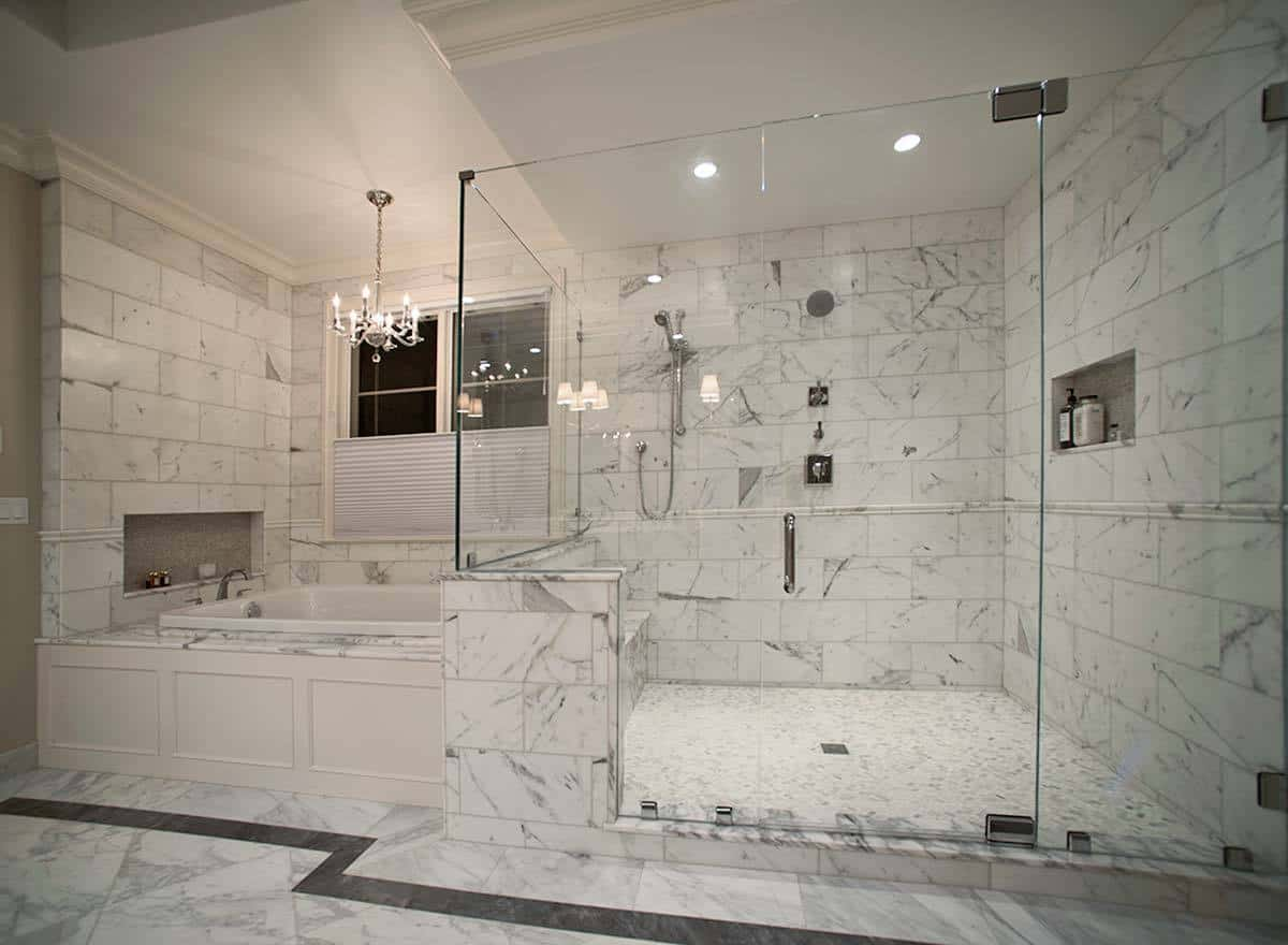 This elegant bathroom is dominated by the white gray marble material that is applied on the flooring and walls. This gives a consistent background for the glass-enclosed shower area and the bathtub beside it that is topped with a simple white chandelier.