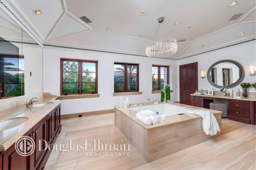 This is a spacious and airy primary bathroom with enough space for the large bathtub to stand in the middle of the beige marble flooring in between the two wooden vanities that has dark wooden hues making it stand out against the white walls. This blends with the white cove ceiling that hangs a crystal chandelier in the middle.
