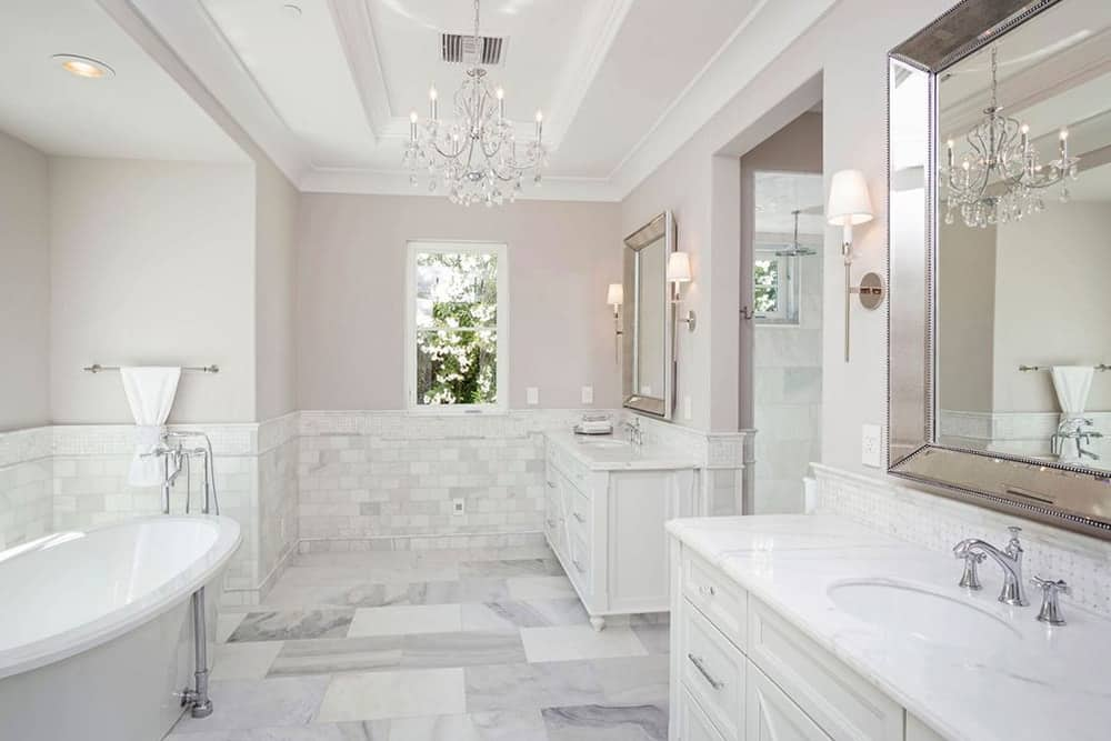 This bright Mediterranean-style bathroom is due to the white marble material of the flooring and walls together with the white wooden vanities and the white freestanding bathtub that are all illuminated by the natural lights coming in from the window augmented by the white chandelier of the white tray ceiling.