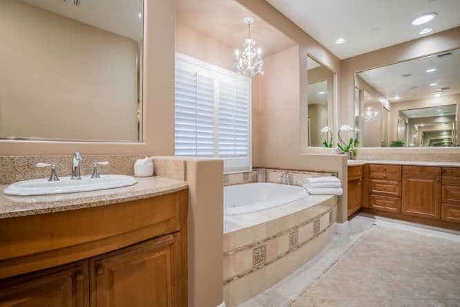 The bathtub of this Mediterranean-style bathroom is topped with a small white chandelier that casts a bright white light that brightens the beige walls that blend with the housing of the bathtub. This sits in between the two wooden vanities paired with large mirrors.