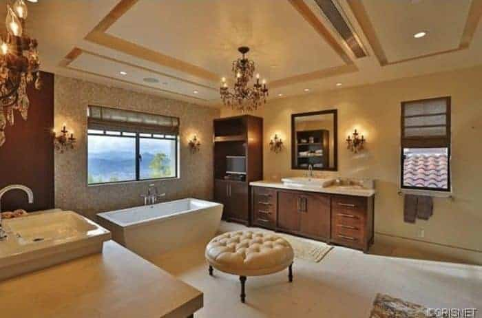 The middle of the tray ceiling has an intricate chandelier that matches with the several wall-mounted lamps on the beige walls flanking the vanity mirrors and the window above the freestanding white bathtub. These are complemented by the wooden elements of the vanity and the shelves beside it.