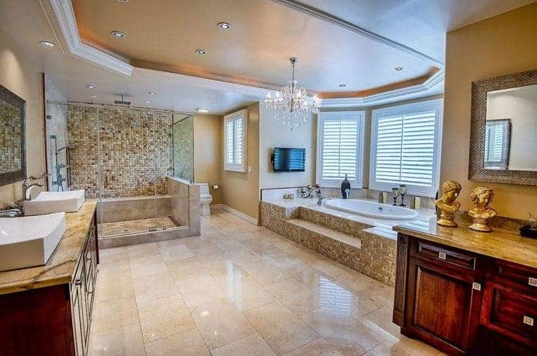 The complex small brown tiles that fill the walls of the shower area matches those that house the bathtub that is placed underneath white shuttered windows. These pairs well with the two-sink vanity with dark brown wooden cabinets that stand out in this Mediterranean-style primary bathroom.