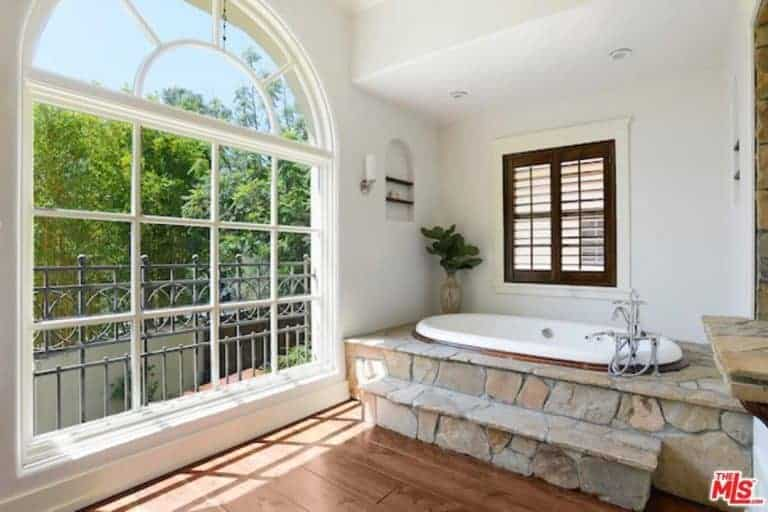 The hardwood flooring that is illuminated by the large arched French window leads to a bathtub that is housed in a raised textured stone structure. This complements the white walls that contrast the dark wooden frame of the shuttered window above the tub.