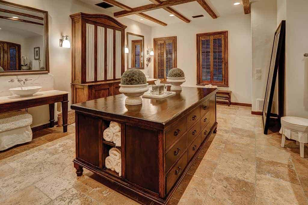 This spacious bathroom has enough space for a dark wooden island in the middle of its textured beige flooring. This structure matches the simple wooden tables of the vanity as well as the large wooden cabinet in the middle. These are all complemented by the exposed wooden beams of the ceiling as well as the shuttered windows.