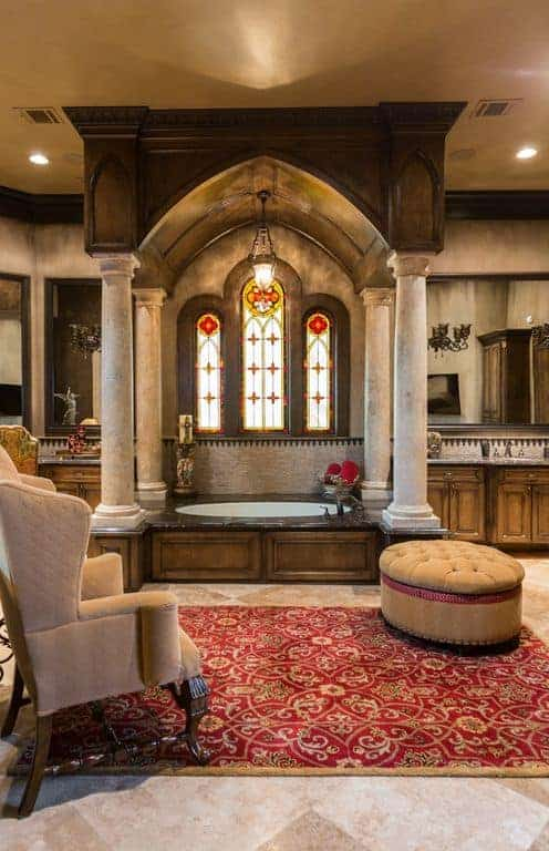 The beige marble flooring is dominated by a bright red patterned area rug that makes the cushioned ottoman and armchair stand out. The bathtub that is in the middle of the two vanities is housed in the same wooden material of the arched ceiling that is supported by stone pillars and adorned with a set of arched windows that has stained glass.