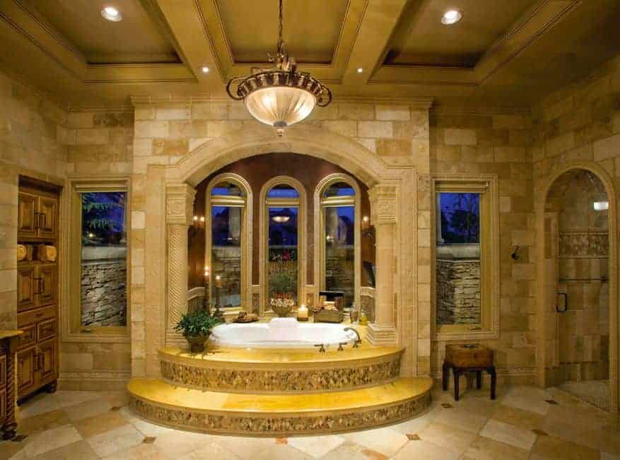 This romantic Meditarranean-style bathroom has golden steps leading to the white porcelain bathtub that is placed in an alcove with arched windows under a beige arch supported by beige columns. This pairs well with the beige marble walls and flooring.