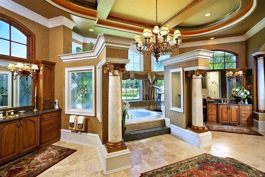 This large Mediterranean-style bathroom has enough space to create a grand entryway for the bathtub alcove. This entryway s guarded on both side with white marble pillars and topped with a majestic chandelier in the middle that hangs from the tray ceiling.