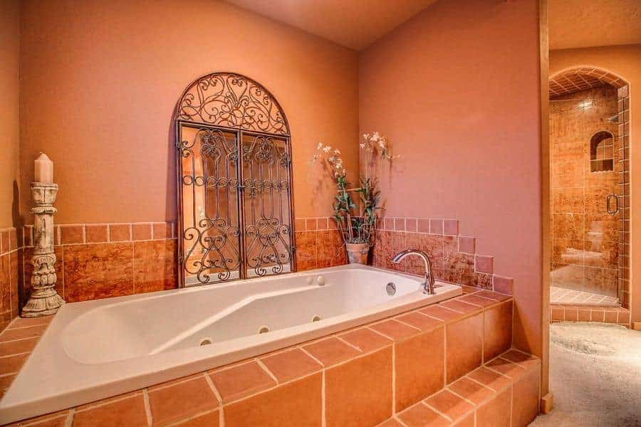 At first glance, you would think that the bathtub is paired with an arched window with intricate wrought iron designs. It is actually a mirror that is leaning against the pink wall beside the tub that is inlaid with tiles of the same hue and adorned with a potted plant and large candelabra on both corners.