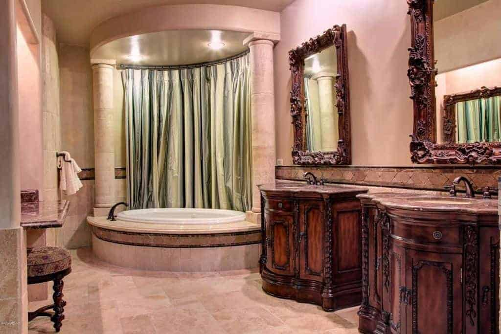 The wonderful pink walls and marble flooring of this Mediterranean-style bathroom are complemented by the dark brown wooden vanities and the frames of the mirrors that have intricate carvings aiming to elevate the elegance of the primary bathroom.