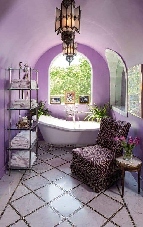 The wonderful cove ceiling has a purple hue that blends with the walls. This pairs well with the pair of Mediterranean-style lantern pendant lights. One hangs over the freestanding bathtub by the arched window while the other hangs over the sitting area that has a cushioned chair with an eclectic animal skin pattern.