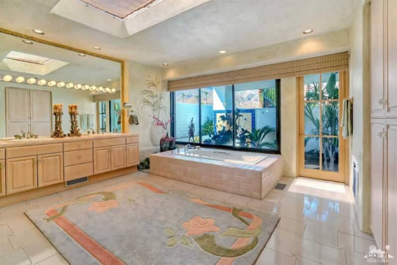 The charming chic floral area rug dominates the white flooring tiles that have a unique jigsaw puzzle pattern to it. This pairs well with the housing of the bathtub that stands out against its large tinted glass window. Adjacent to this is the large wooden two-sink vanity with a massive built-in mirror lined with bulbs.