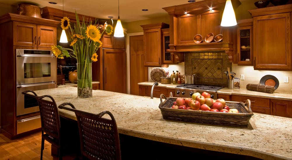 A focused shot at this kitchen's center island with a breakfast bar featuring a stylish countertop. It has a sunflower table decor and is lighted by pendant lights.