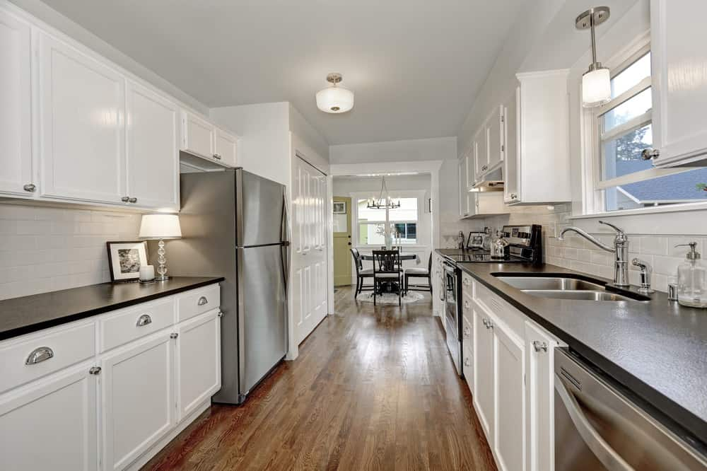 A narrow kitchen-style with white cabinetry and black kitchen countertops. The area has hardwood flooring.