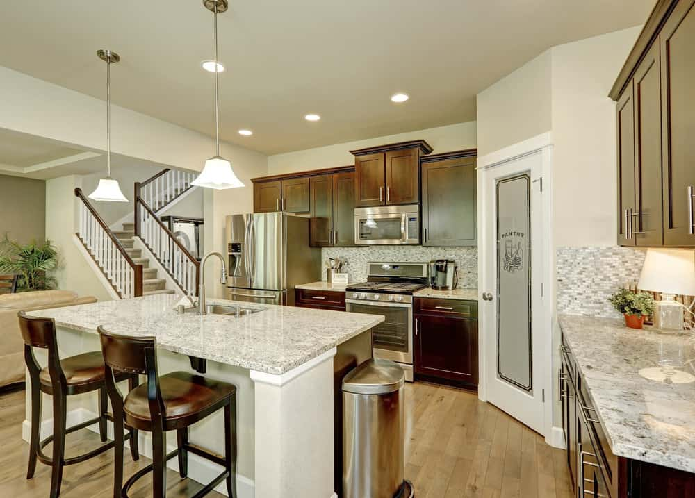 This kitchen features a center island with a marble countertop matching the kitchen counters' countertops. The kitchen also has wooden cabinetry.