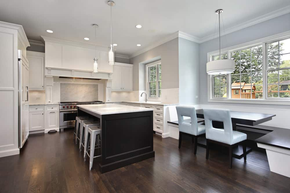 U-shaped kitchen with hardwood flooring and gray walls. It features a center island with a breakfast bar along with a dining nook on the side.